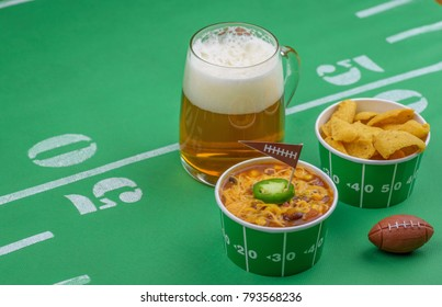 bowl of chili, chips, and beer on table decorated for superbowl party