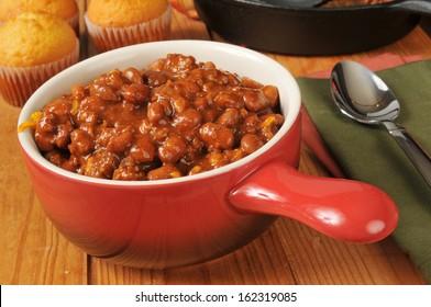 A bowl of chili con carne with cornbread muffins