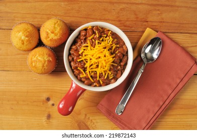 A bowl of chili and cornbread from a high angle view on a rustic wooden table