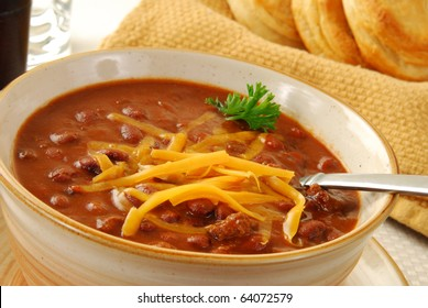 A bowl of chili with melted cheese