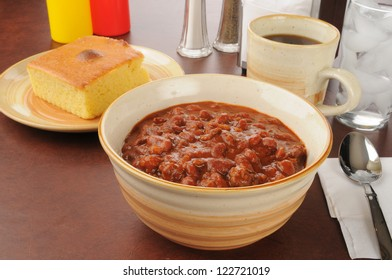 A bowl of chili with a slice of cornbread