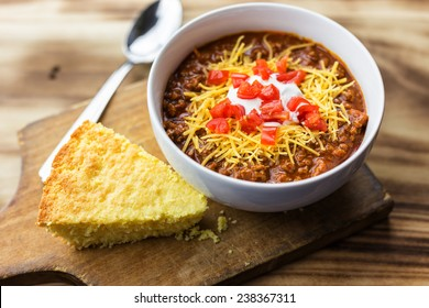 A bowl of chili with tomatoes, sour cream, cheese and a piece of cornbread against a wooden background.