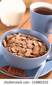 Bowl of chocolate corn flakes cereal with spoon and chocolate bars, a cup of tea and a jug of milk in the back (Selective Focus, Focus in the middle of the cereal)