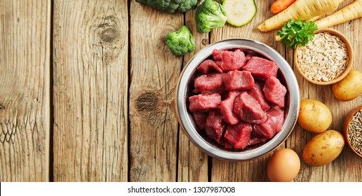 Bowl of chopped raw meat for a dog or cat on a rustic wood floor surrounded by fresh vegetables for a healthy animal diet