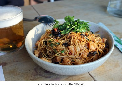 a bowl of chow mien noodles with beer in background at La Furgo in Cordoba, Spain