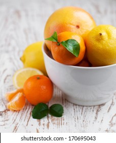 Bowl with Citrus Fruits with leaves on table
