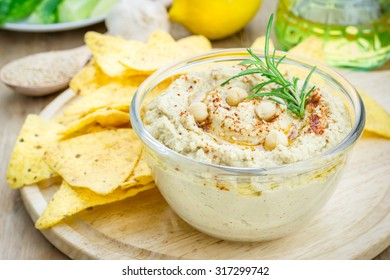 Bowl of classic hummus sprinkled with paprika and sesame, served with tortilla chips