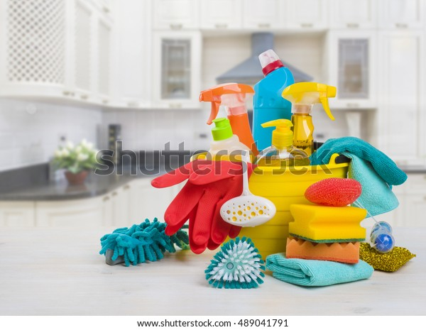 Bowl with cleaning products on table over blurred kitchen background