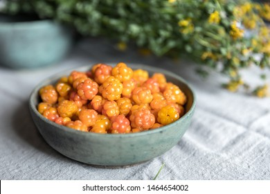 A bowl of cloudberry and dried Hypericum on the table. Background gray linen.