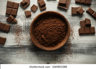 Bowl with cocoa powder and tasty chocolate on wooden background, top view