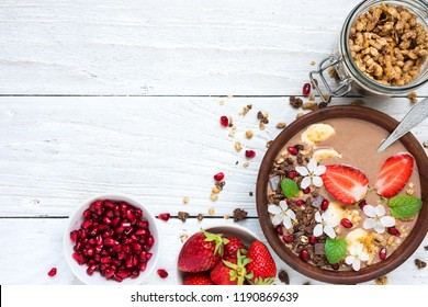 bowl of cocoa smoothie with chocolate granola, banana, strawberry and pomegranate topped with mint and flowers with a spoon for healthy breakfast. top view with copy space