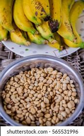 A bowl of coffee grains next to the fresh banana