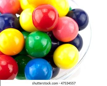 Bowl of colorful gumballs on white