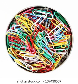 A bowl of colorful paperclips, white background