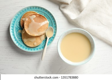 Bowl of condensed milk and pancakes served on wooden table, top view. Dairy products