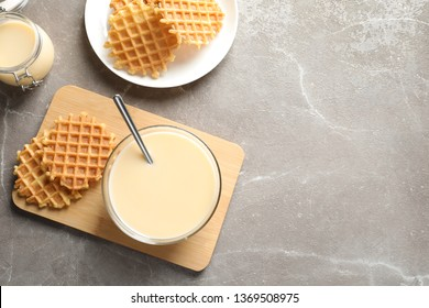 Bowl of condensed milk and waffles served on grey table, top view with space for text. Dairy products