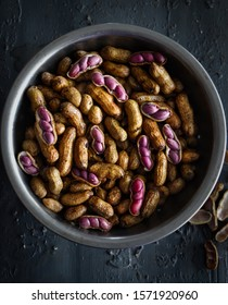 A bowl containing boiled peanuts or groundnuts, some shelled and with pink peanuts showing, on a grey background