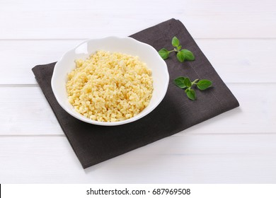 Bowl of Cooked whole groats on gray placemat
