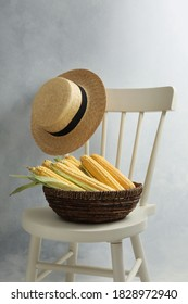 Bowl of corn cobs on chair near grey wall