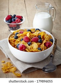 Bowl of corn flakes and fresh berries and jug of milk on  wooden background