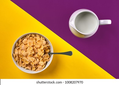 Bowl with corn flakes, jug of milk and spoon on purple and yellow background, top view