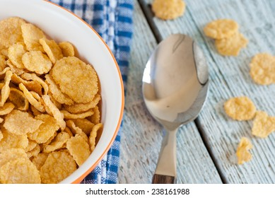 Bowl of corn flakes with spoon and towel on old wooden table
