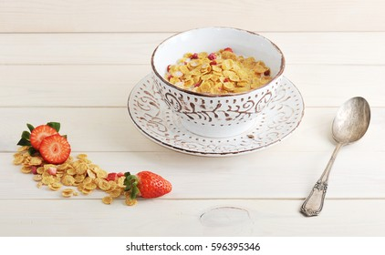 bowl with corn flakes and strawberries with milk on wooden white background