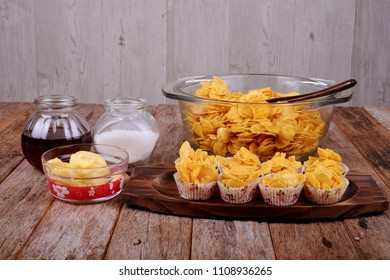 Bowl with cornflakes, conflakes cup, suger, butter and honey on  wooden background