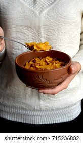 Bowl of cornflakes in female hands