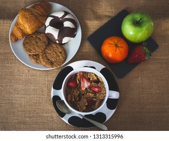 A bowl with cornflakes and red berries and a plate of black slate with a green apple, a tangerine and a strawberry and one plate with one croissant, one chocolate donut and cookies on a burlap