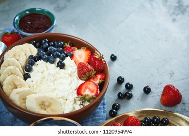 bowl of cottage cheese with berries, bananas, jam and sour cream, fresh berries and cottage for breakfast, horizontal. top view of a dishes with food on the dark concrete backdrop, copyspace.