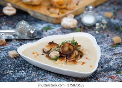 Bowl of cream mushroom soup with fried mushrooms
