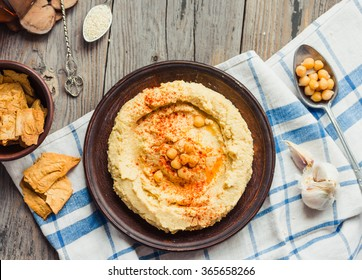 A bowl of creamy hummus with olive oil,garlic, paprika and pita chips,top view,rustic background