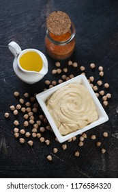 Bowl of creamy hummus with raw chickpeas, paprika and olive oil. High angle view on a dark brown stone surface
