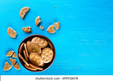 A bowl with crispy crackers on a blue background. View from above. The concept of a healthy diet.