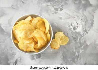 Bowl with crispy potato chips on grey table, top view