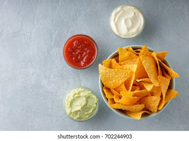 Bowl of crusty nachos or tortilla with different dipping sauces on gray stone background. Mexican snacks ready to eat. Top view with copy space.