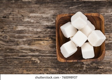 Bowl with cubes of white sugar on an old wooden background, top view