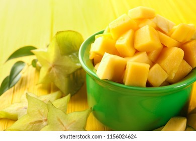 Bowl with cut fresh mango and starfruit on color wooden table, closeup