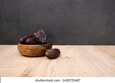 Bowl of dates, date fruits in the plate, dates aligned left with copy space area for text