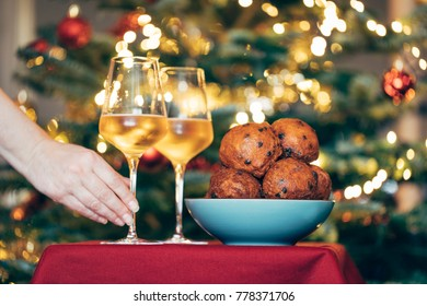 Bowl with deep fried rasin buns, traditionally eaten in the Netherlands around New Year's eve. Two glasses with  sparkling wine and a hand reaching. Decorated christmas tree in the background