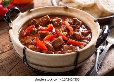 A bowl of delicious authentic Hungarian goulash with bread dumplings and red pepper garnish.