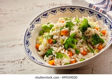 Bowl of delicious cooked rice, peas, carrots, broccoli, parsley beside cloth napkin on weathered table