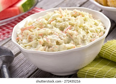 A bowl of delicious creamy homemade coleslaw on a rustic picnic table with watermelon and corn.