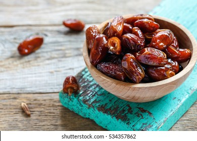 Bowl with delicious dried dates on old wooden board.