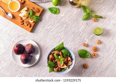 Bowl with delicious fig salad and ingredients on light table