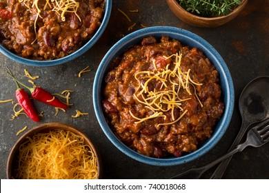 Uma tigela de delicioso chili caseiro feito com carne moída, feijão, pimenta vermelha, tomate e queijo cheddar ralado.