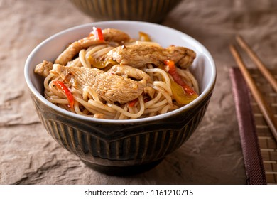 A bowl of delicious honey garlic noodles with chicken and peppers.