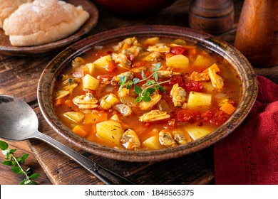 A bowl of delicious Manhattan clam chowder with fresh thyme garnish on a rustic wood table.
