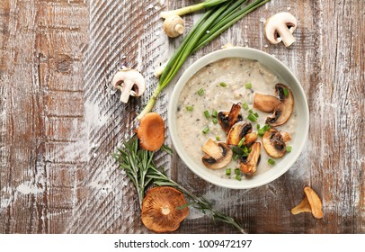 Bowl with delicious mushroom soup on wooden table